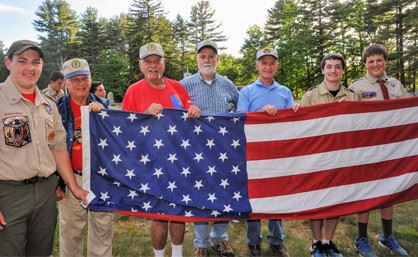A group of people posing for a picture while holding up an american flag