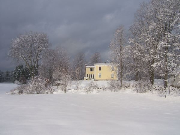 Snow Covered Field With Yellow House in Background